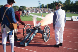 UNH alumnus Dick Dewing '53 and assistants shoot off the cannon at a UNH football game