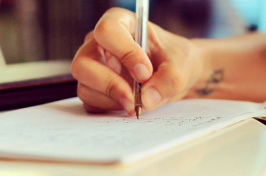 a close-up of a person writing in a notebook