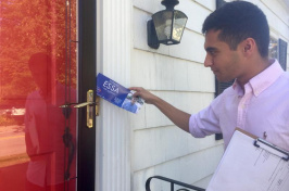 UNH Manchester student Hassan Essa putting a flyer in someone's door