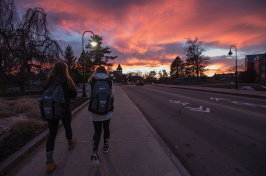 UNH students walking on Garrison Avenue against a colorful sunset over Thompson Hall
