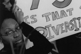a UNH student holding a poster calling for increased recruitment of minority students and faculty (Photo: University Archives)