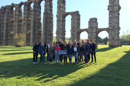 Charlotte Harris '18 and other UNH students in front of an aqueduct in Spain
