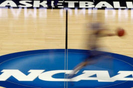 A player runs across the NCAA logo during practice in Pittsburgh before an NCAA tournament basketball game in 2012. (Keith Srakocic / Associated Press)