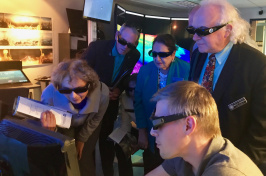 Small group of peope wearing 3D glasses crowd around a computer