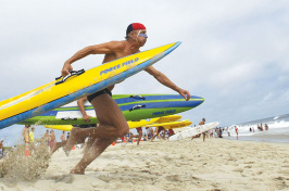 UNH alumnus Greg Johnson '83 running with a surfboard at the beach (photo: Cape Cod Times)