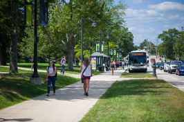 UNH students walking down Main Street by Thompson Hall Lawn in Durham