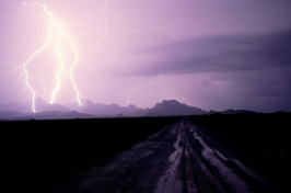 lightning against a purple sky and mountainous landscape (Bruce Dale/National Geographic Creative)