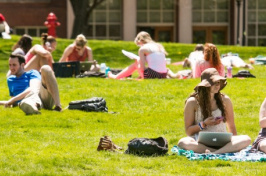 UNH students sitting on Thompson Hall lawn