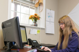A member of the UNH community at work at a computer