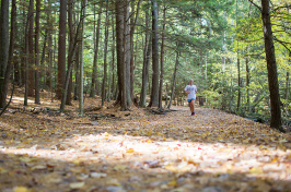 a UNH student running in College Woods