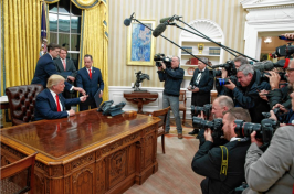 President Donald Trump hands over his pen after signing his first executive order in the Oval Office of the White House in Washington on Jan. 20. AP