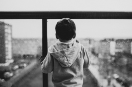 Image of child looking out a window