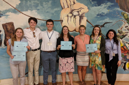 students and leader holding awards