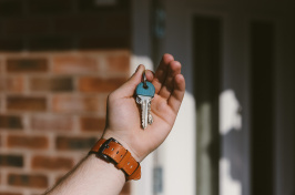 Image of a person  holding a key to a house