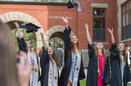 UNH graduates tossing caps in front of Thompson Hall on Durham campus