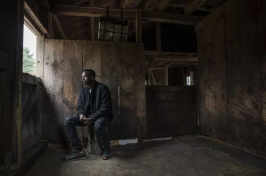 Abdi Nor Iftin, a Somali refugee, in the Maine barn where he cared for horses and chopped wood (Greta Rybus for The Boston Globe)