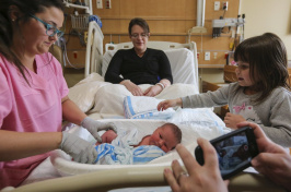 Image of people surrounding a newborn