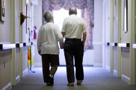 Image of two elderly people walking hand-in-hand down hall