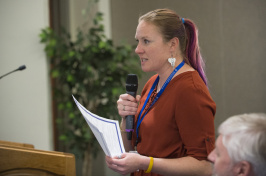 Postdoctoral researcher Kerri Seger speaks into a microphone