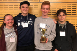 photo of four students with trophy