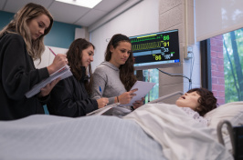"Students standing at the side of the ""patient's"" bed."