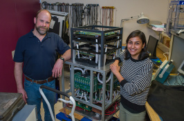 An older man with a beard and a younger woman with dark chin-length hair stand beside a tall cube machine they built.