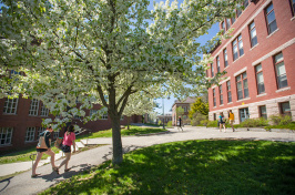 UNH students walking by the library and Thompson Hall in spring