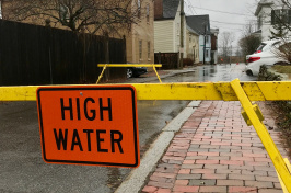 "Flooded road blocked with yellow tape and ""high water"" sign"
