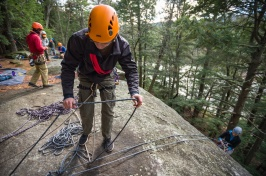 Student in orange helmet perched on edge of rock, about to rappel down