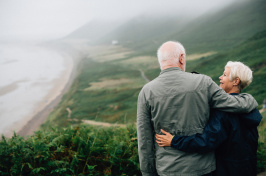 Image of two people looking from a mountain at a beach