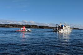 Autonomous surface vehicle at sea behind a research vessel