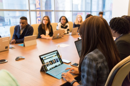 Image of people sitting in a conference room.