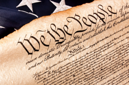 A photo of the U.S. Constitution with a flag