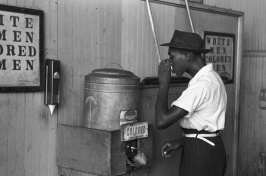 "African American man drinking water from a keg labeled ""colored"""