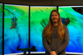 Drew Stevens stands in front of large computer screens.