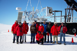Team of researchers in Antarctica stand in front of a large telescope.