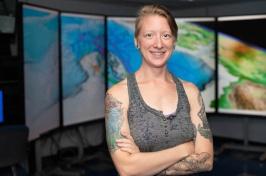 Lynette Davis standing in front of seafloor maps