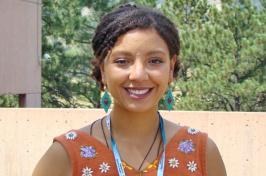 Tamara Marcus smiles at the camera wearing an orange printed top