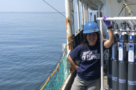 UNH grad student Melissa Melendez stands on the deck of a research vessel.