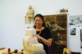Sachiko Akiyama works on a large wood sculpture