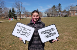 A UNH student holds a step out sign