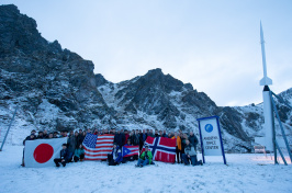 Students hold up their country's flags next to white rocket and snow-capped peaks nearby.