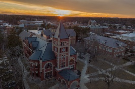 Thompson Hall on UNH campus shot from above, with sun setting behind
