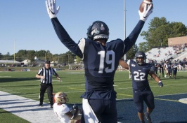 UNH football player holding football in the air