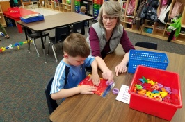 Photo of a teacher working with a student at a table in a classroom