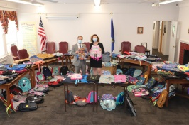 Two lawmakers hold up backpacks that were donated during an annual backpack drive.
