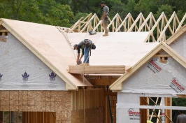 An image of two roofers working on the roof of a house that's under construction.