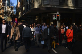 Women and men of different backgrounds cross a busy street in a city.