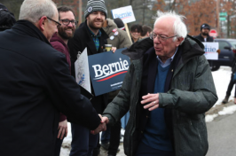 Bernie Sanders shakes hands with supports outside.