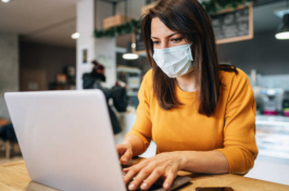 A women wearing a mask sits at a laptop
